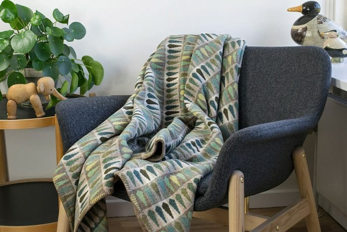 Vibrant green wool throw with leaf pattern in chair