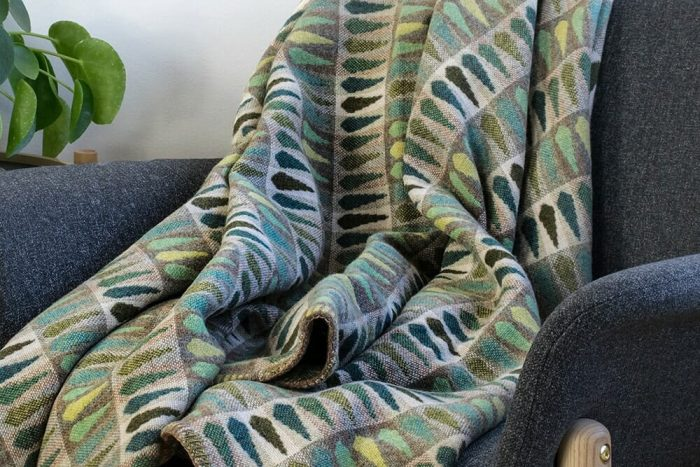 Vibrant green wool throw with leaf pattern in chair with details