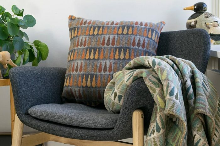 Vibrant green wool throw with leaf pattern with Copper and Gray cushion