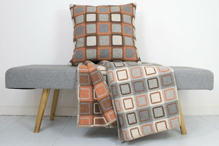Reversible Wool Throw in soft oranges with sofa cushion